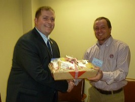 State Senator Whitney Westerfield receives a food basket of Kentucky agricultural food products from Logan County Farm Bureau President Jeremy Robertson