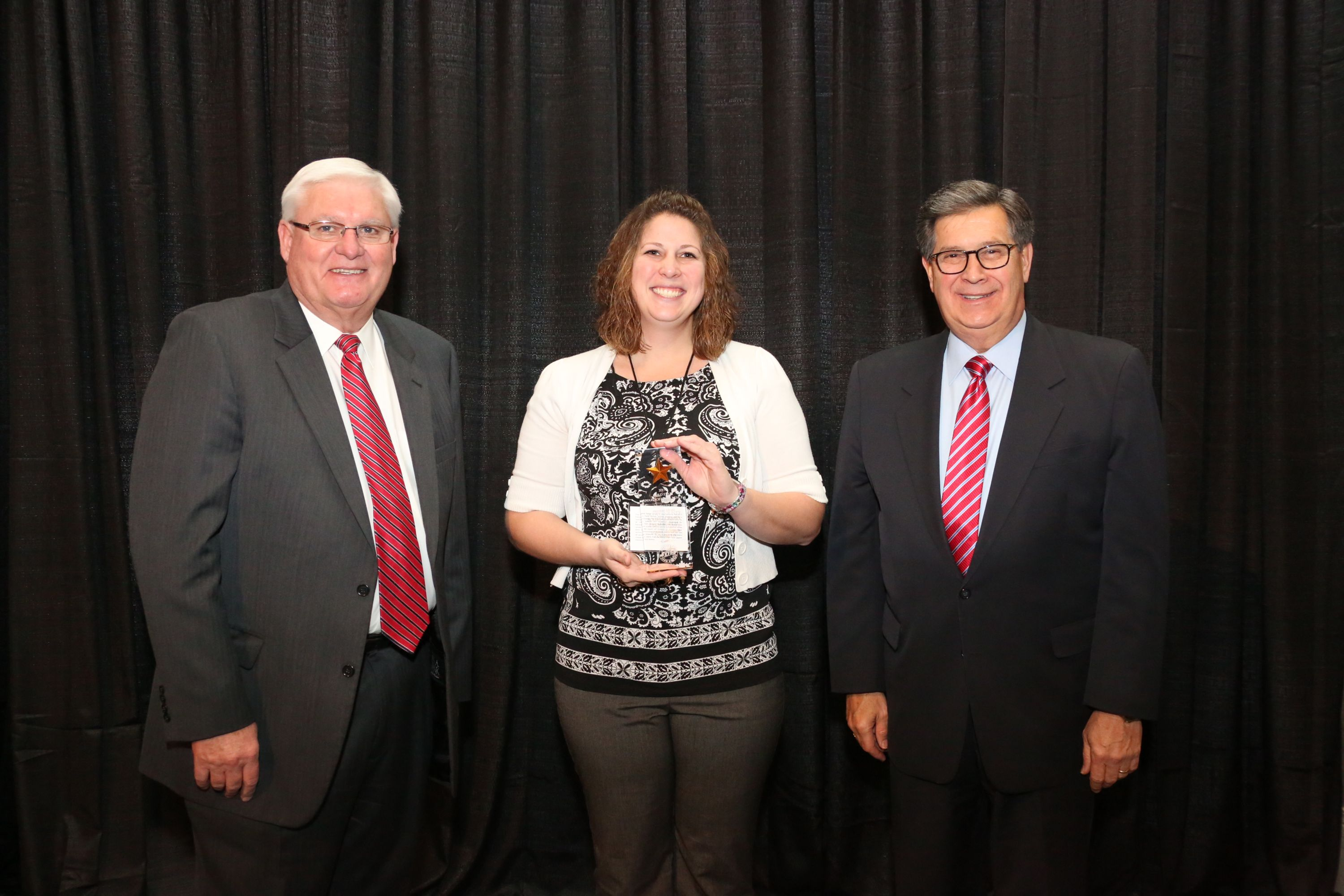 Michelle Simon of Scott County accepts the Gold Star Award of Excellence from Mark Haney, Kentucky Farm Bureau President, and David S. Beck, Kentucky Farm Bureau Executive Vice President.