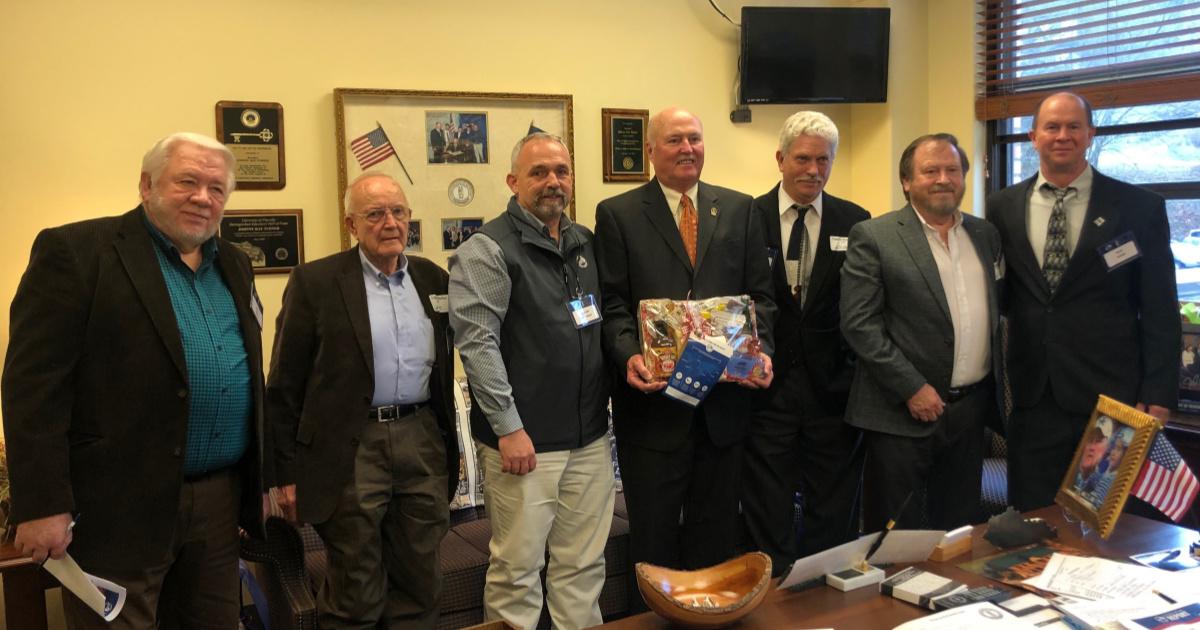 Kentucky Senator Johnny Ray Turner receives a basket of Kentucky agricultural products from Kentucky Farm Bureau.