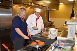 Amanda Langlitz assists sous chef Darwin Gross in preparing a lunch at Transylvania University.